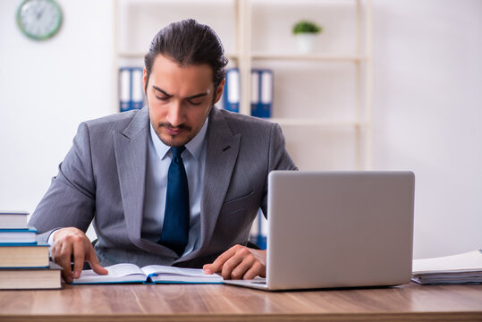 Young male businessman reading books at workplace