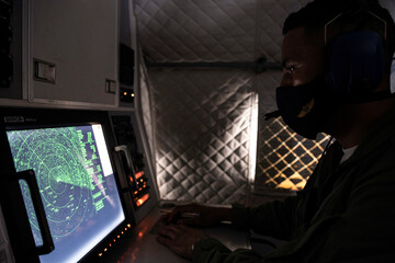 An Ecuadorian navy officer looks at a radar after a fishing fleet of mostly Chinese-flagged ships was detected in an international corridor that borders the Galapagos Islands' exclusive economic zone, in the Pacific Ocean