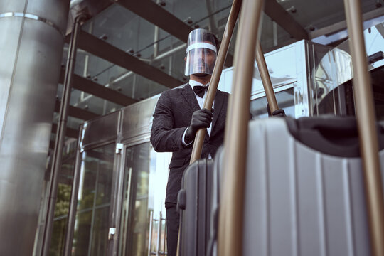 Hotel worker in protective equipment operating a heavy trolley