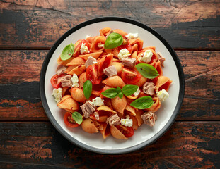 Conchiglie Tuna pasta with tomato sauce, feta cheese and basil on wooden table.