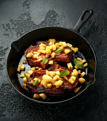 Roasted Pork chops with caramelized apples, walnuts and sage in a cast iron pan