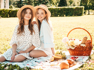 Two young beautiful hipster woman in trendy summer sundress and hats. Carefree women making picnic...