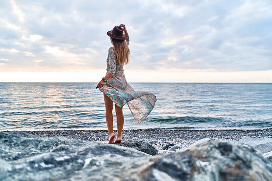 Boho chic woman in long fluttering dress and felt hat standing back on stone by the sea