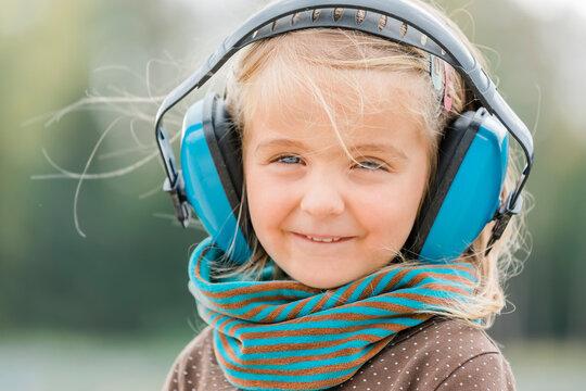 Happy toddler girl wearing earmuffs