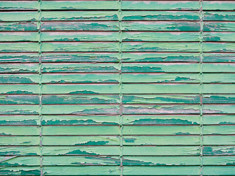 Background of a typical rough, shabby and aged green wood slat door shutter blind