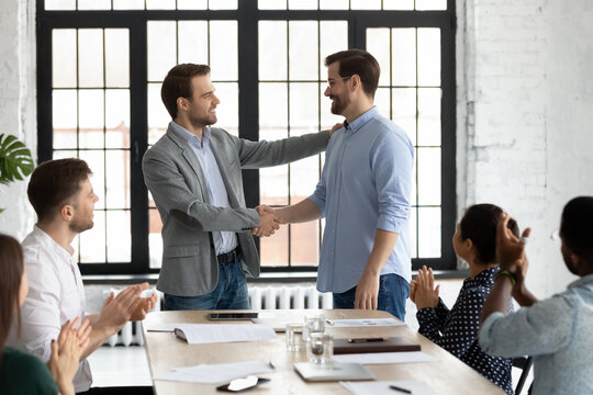Smiling executive shaking successful employee hand, congratulating with job promotion, thanking for good work results, diverse employees applauding to colleague, appreciation and recognition