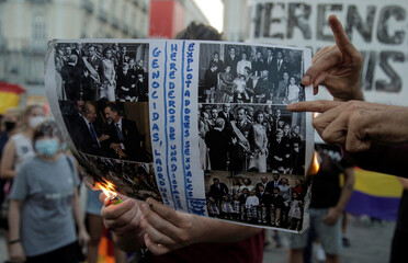 A protester destroys a picture of the royal family by a fire during a march against Spain's monarchy amid an investigation into Juan Carlos' involvement in a high-speed rail contract in Saudi Arabia, in Madrid