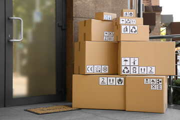 Cardboard boxes with different packaging symbols on porch near entrance. Parcel delivery
