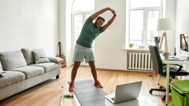 Personal trainer. Full length shot of male fitness instructor stretching his body while streaming, broadcasting video lesson on training at home using laptop. Sport, online gym concept