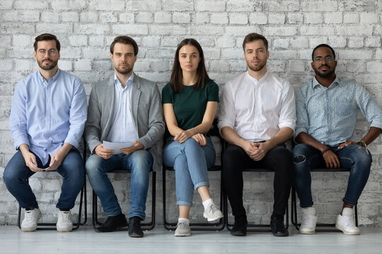Portrait of confident diverse candidates sitting in row in queue, serious applicants business people waiting for job interview, looking at camera, employments and recruitment concept