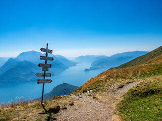 Trail signs on a path in the alps of Lake Como