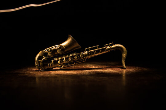 Alto gold sax miniature with colorful toned light on foggy background. Saxophone music instrument in lowlight. Selective focus