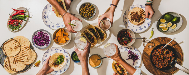Foto op Aluminium Eten Friends having Mexican Taco dinner. Flat-lay of beef tacos, tomato salsa, tortillas, beer, snacks and peoples hands clinking glasses over white table, top view. Mexican cuisine, comfort food concept