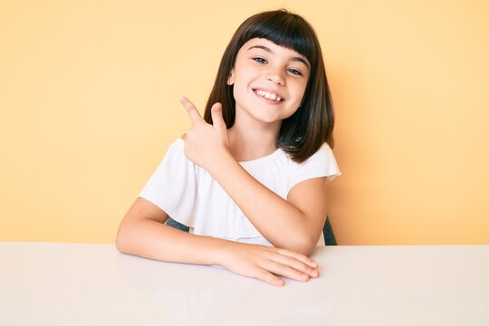 Young little girl with bang wearing casual clothes sitting on the table smiling cheerful pointing with hand and finger up to the side