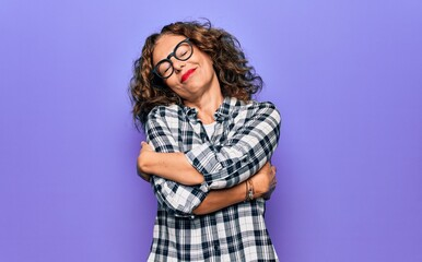 Middle age beautiful woman wearing casual shirt and glasses over isolated purple background hugging...