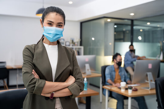 Asian young businesswoman wearing mask working on computer in office.