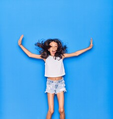 Adorable hispanic child girl wearing casual clothes smiling happy. Jumping with smile on face over isolated blue background