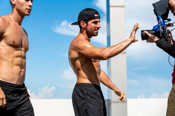 Hispanic athletic man fitness vlogger with friends recording video on rooftop for outdoor exercise concept