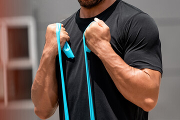 Fit muscular sports man doing bicep curl exercise with resistance band outdoors at home in sunlight