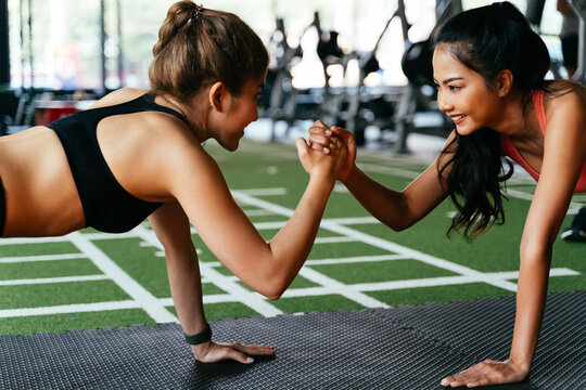 Healthy smiling female supportive friends giving high five to each other while pushing up in the fitness gym. Asian sporty people working out together. Teamwork and achievement concept