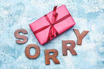 Gift with word SORRY on color background