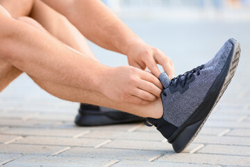 Sporty young man tying shoelaces outdoors, closeup