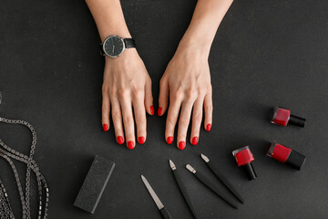 Hands and tools for manicure on dark background