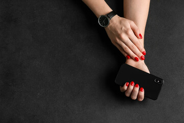 Hands with beautiful manicure and mobile phone on dark background