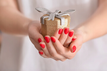 Woman with beautiful manicure holding gift, closeup