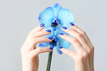 Hands with beautiful manicure and flowers on light background