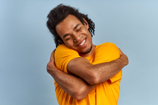 Handsome dark skinned young man in a yellow t-shirt hugs himself on a blue background. Guy with his eyes closed feels happy and positive, smiling confidently. Concept of selfishness and self-care.