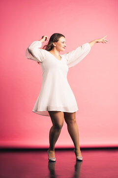 Happy plus size fashion model in white dress dancing on pink background