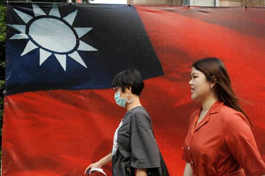 People walk past a Taiwan flag in Taipei