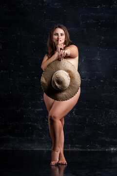 Naked sexy plus size model hiding behind hat on black background