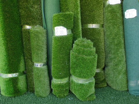 collection of rolls of artificial turf hold together with plastic tape