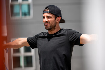 Handsome athletic Latino man doing stretching exercise outdoors at home