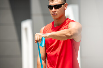 Handsome sports man doing shoulder front raise exercise with resistance band outdoors in the sun