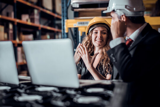 Engineer woman and businessman wearing a hardhat standing cargo at goods warehouse and check for control loading from Cargo freight ship for import and export by report on laptop. Teamwork concept