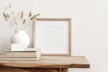 Square wooden frame mockup on vintage bench, table. Modern white ceramic vase with dry Lagurus ovatus grass, books and busines card. White wall background. Scandinavian interior.