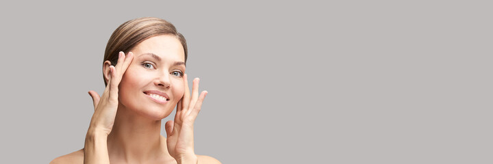 Happy pretty woman. Hands near face. Skincare concept. Home morning routine. Clean skin. Cream...