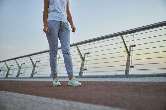 Sportswoman in stylish jogging shoes on a footbridge