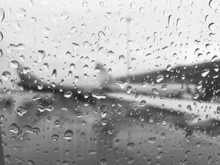 The blurred wing of the plane is visible through a drop of rain on the window of the aircraft