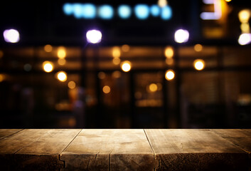 background Image of wooden table in front of abstract blurred restaurant lights Fotomurales