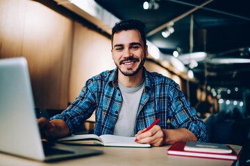 Portrait of cheerful male student enjoying learning in coworking office using laptop computer for research,happy freelancer looking at camera during making project for remote job making notes.
