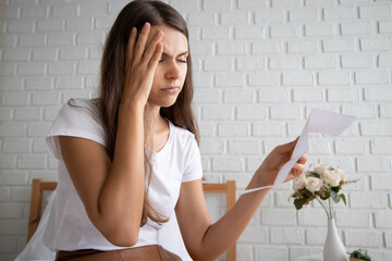 frustrated, shocked, stressed women with expensive bill, debt invoice, eviction notice; concept of high cost of living, expensive bill, getting busted, economic recession, no job no money