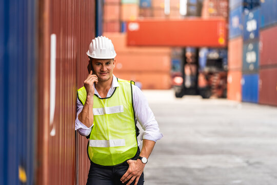 Portrit worker engineer standing use a mobile phone and checking the containers box from cargo ship for export and import