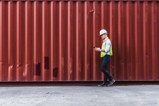 Portrit worker engineer walking to checking the containers box from cargo ship for export and import