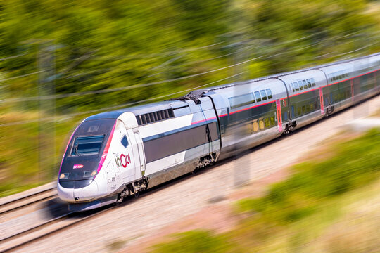 Ver-sur-Launette, France - July 29, 2020: A TGV Duplex inOui high speed train from french rail company SNCF is driving at full speed in the countryside (artist's impression).