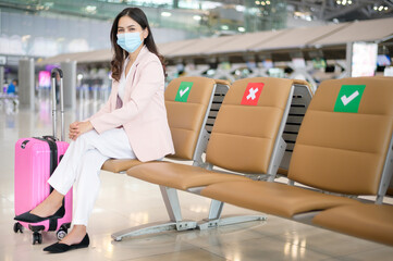 A business woman is wearing protective mask in International airport, travel under Covid-19...