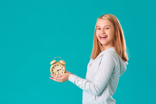 A teenage girl holds an alarm clock, standing on an isolated turquoise background, very happy and excited, the expression of a winner , she celebrates the victory by shouting with a big smile